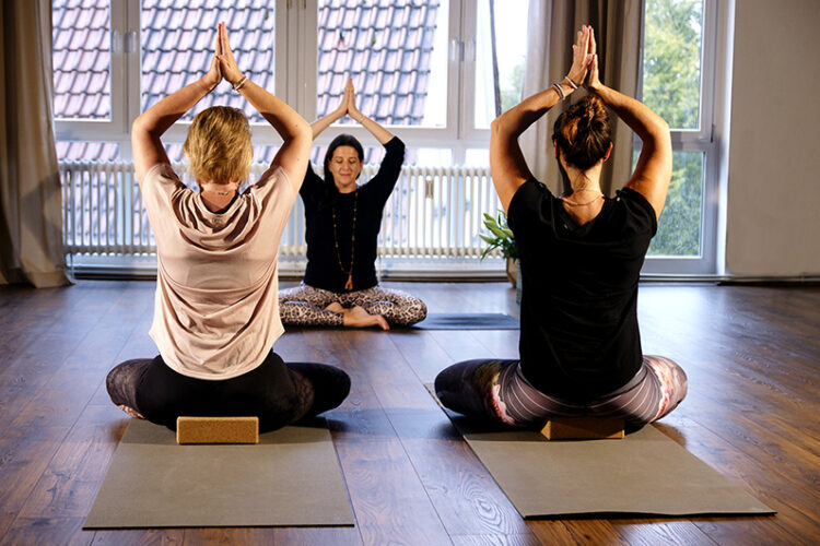 Frauen entspannen im Yogaraum Ravensburg mit Vinyasa Yoga.