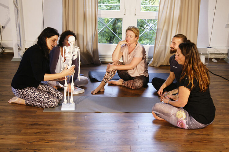Die Lehrerin der Prenatal Yoga Ausbildung und Weiterbildung erkärt den Schülerinen den menschlichen Körperbau.