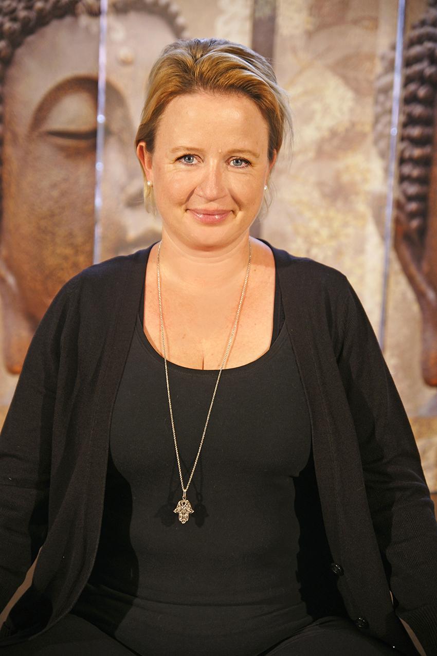 Yoga Lehrerin Andrea aus dem Yogaraum Ravensburg hat blonde Haare und lächelt.