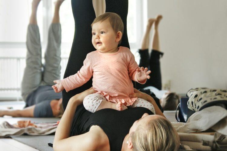Frau beim Rückbildungsyoga. Sie liegt auf dem Rücken ihr Baby sitzt auf ihrem Bauch.