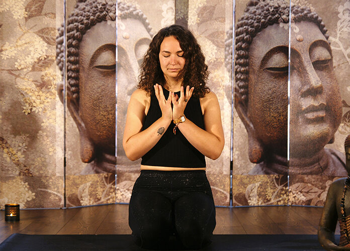 Frau kniet auf einer Matte während sie eine Meditation macht.