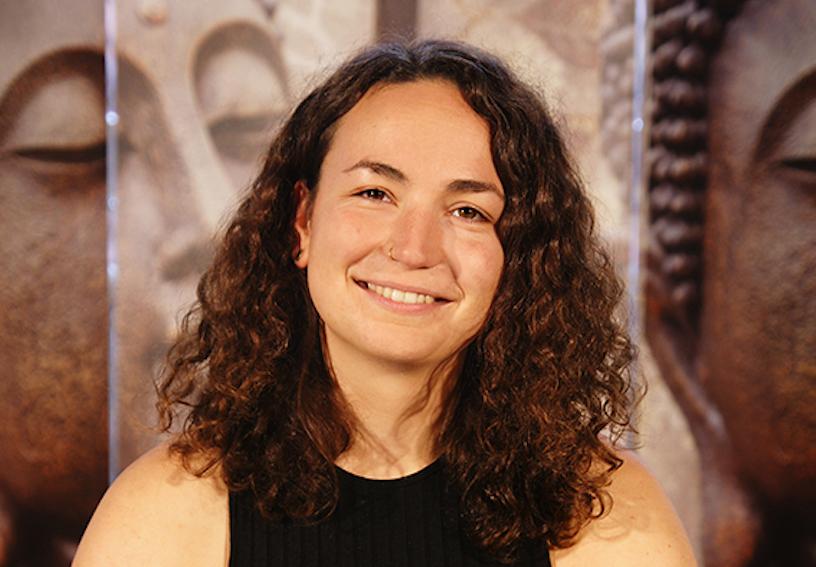 Yoga Lehrerin Charlotte aus dem Yogaraum Ravensburg trägt ein schwarzes Top und hat braune, lockige Haare.
