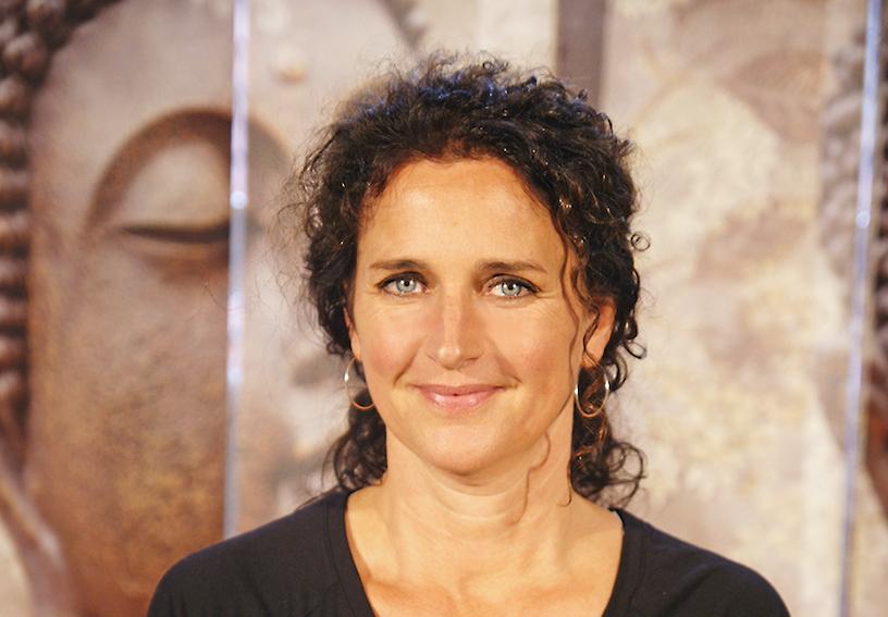 Yoga Lehrerin Nani aus dem Yogaraum Ravensburg hat braune, lockige Haare, zusammengebunden zu einem Pferdeschwanz.