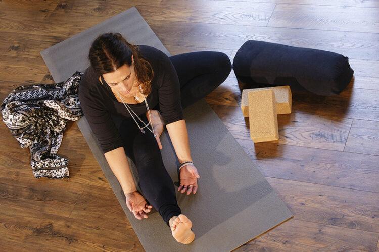Frau sitzt auf der Yogamatte und macht Yin Yoga im Yogaraum Ravensburg.