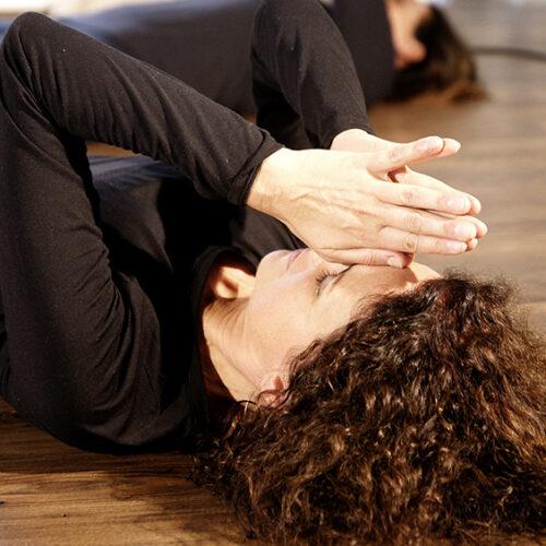 Eine Frau liegt mir gefalteten Händen am Boden und entspannt beim Yoga Kurs für Anfänger im Yogaraum Ravensburg.