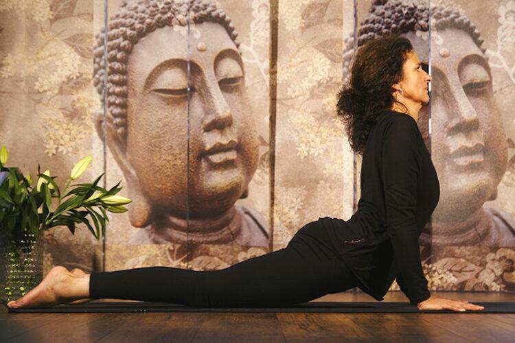 Die Lehrerin führt im Yogaraum Ravensburg eine Anfängerübung vor, für alle die Yoga lernen möchten.