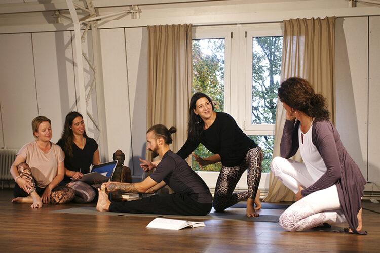Angehende Yoga Lehrer bei der Yoga Ausbildung sitzen auf dem Boden und lernen neu Übungen.