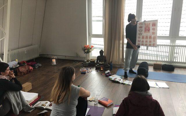 Eine Yoga Lehrerin gibt Einblicke in die Theorie während einem Yoga Workshop im Yogaraum Ravensburg.