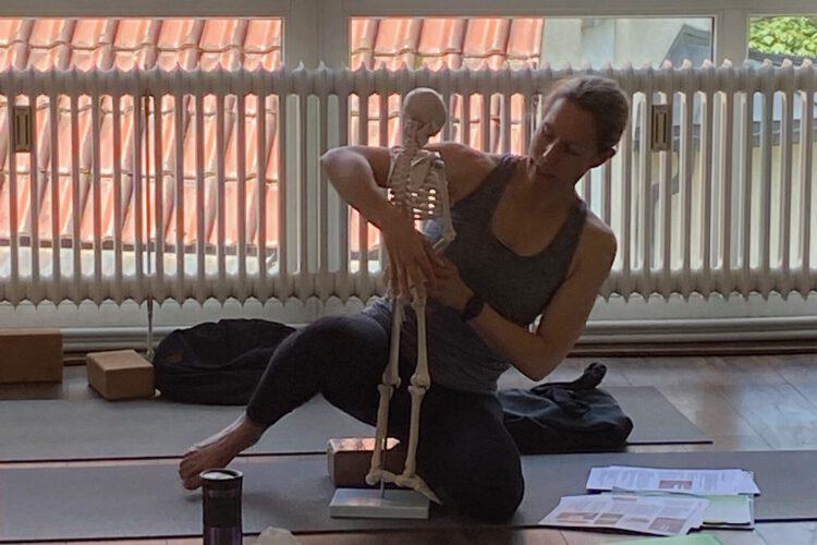 Eine Lehrerin erklärt den menschlichen Körperbau mit einem Modell bei einem spezial Yoga Workshop im Yogaraum Ravensburg.