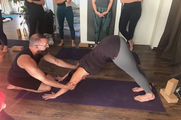 Yoga Lehrer gibt einer Frau Hilfestellung bei einem Asana im Yoga Workshop im Yogaraum Ravensburg.