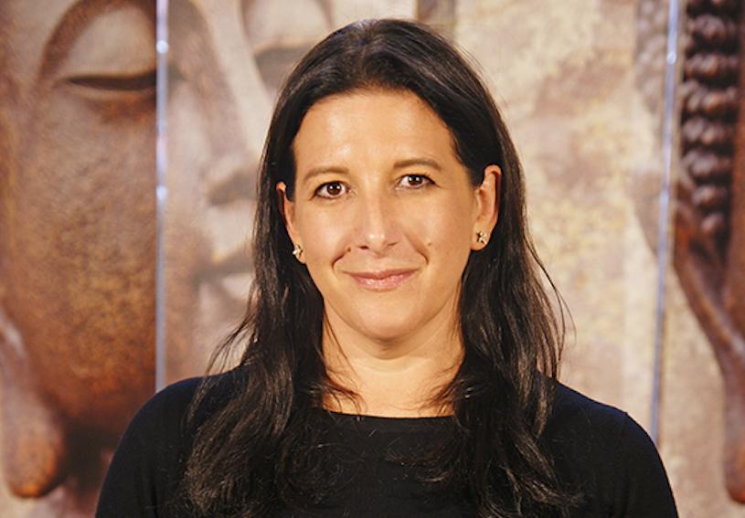 Yoga Lehrerin Ina aus dem Yogaraum Ravensburg trägt einen schwarzen Pullover und lächelt.