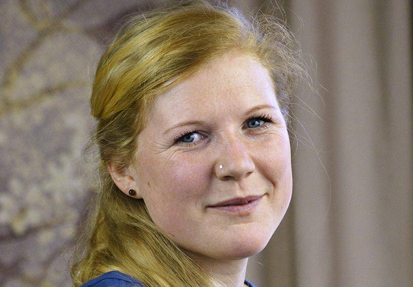 Yoga Lehrerin Inke aus dem Yogaraum Ravensburg trägt einen blauen Pullover und lächelt.