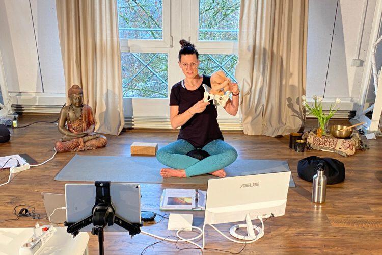 Eine Yoga Lehrerin erkärt im Yoga Workshop im Yogaraum Ravensburg den Körperbau einer Hüfte an einem Modell.