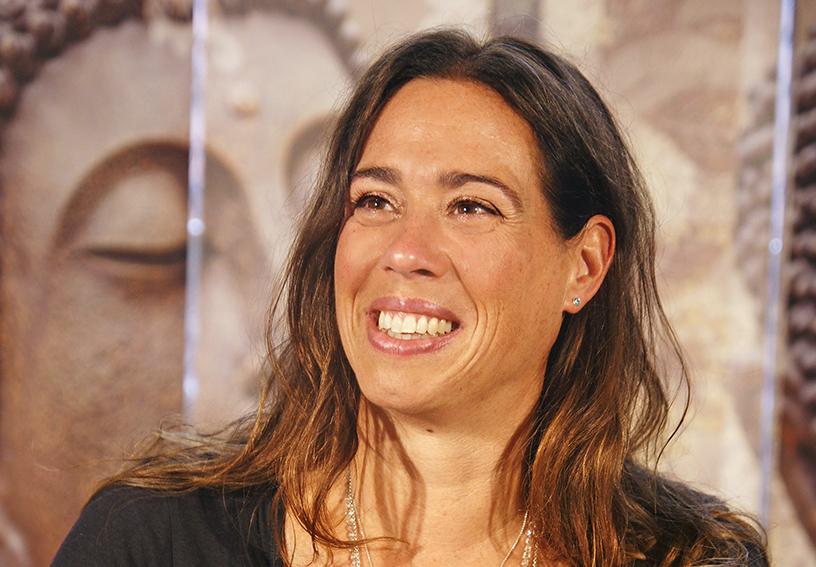 Yoga Lehrerin Marion aus dem Yogaraum Ravensburg blickt lächelnd zu linken Seite.