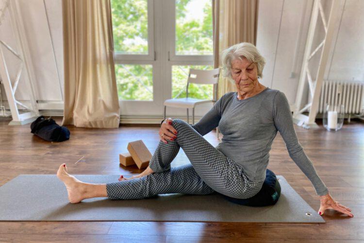 Frau macht Dehnübungen im Kurs Yoga für Senioren im Yogaraum Ravensburg.