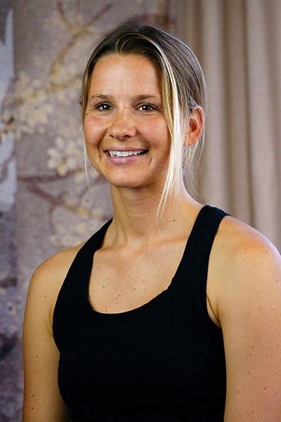 Yoga Lehrerin Steffi aus dem Yogaraum Ravensburg hat blonde Haare und braune Haut.